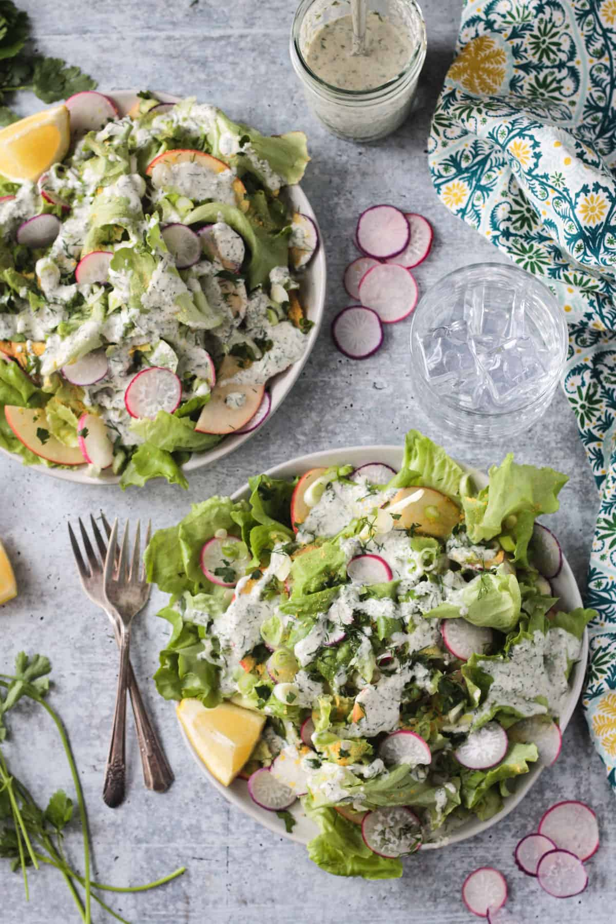 Tablescape with two bowls of salad surrounded by sliced radishes and lemon wedges.