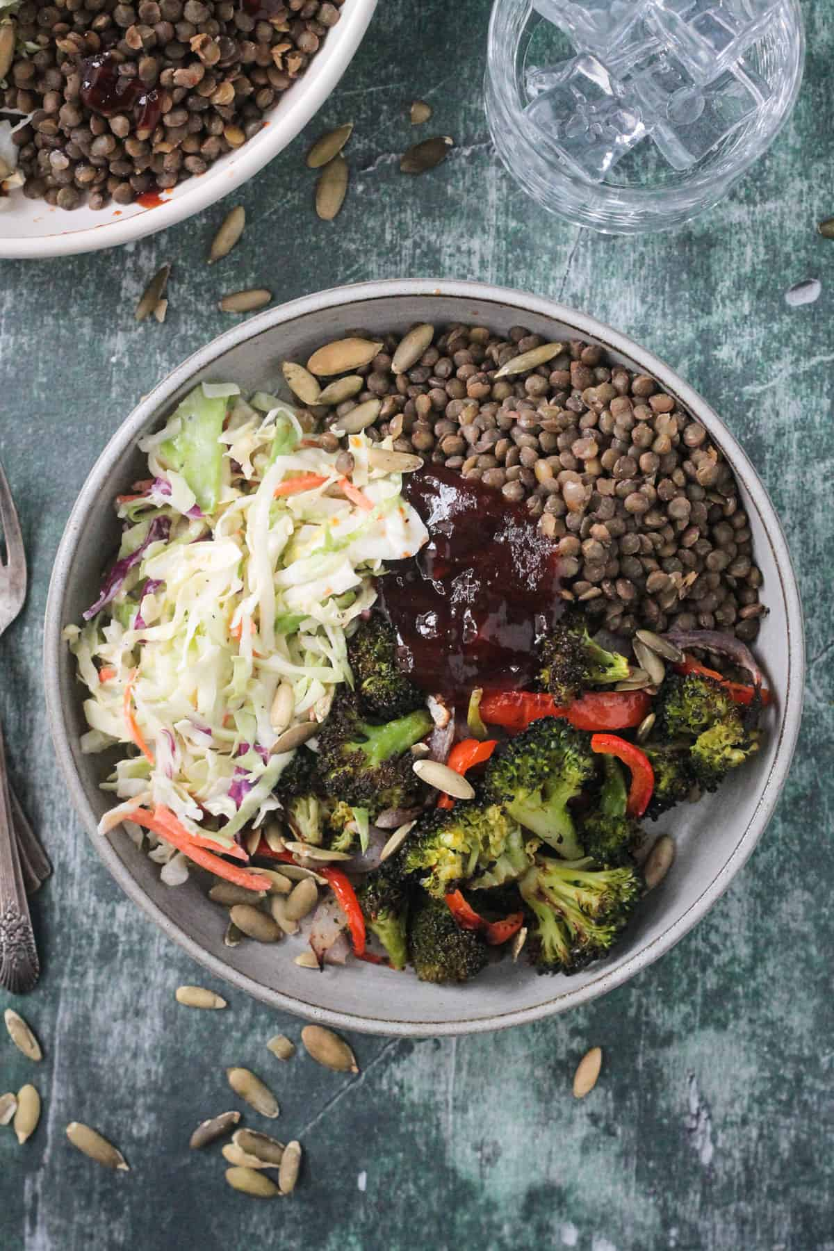 Lentils, coleslaw, roasted broccoli, and bbq sauce in a gray flat bowl.