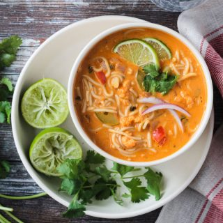 Red Curry Thai Noodle Soup in a white bowl next to two lime halves and cilantro leaves.