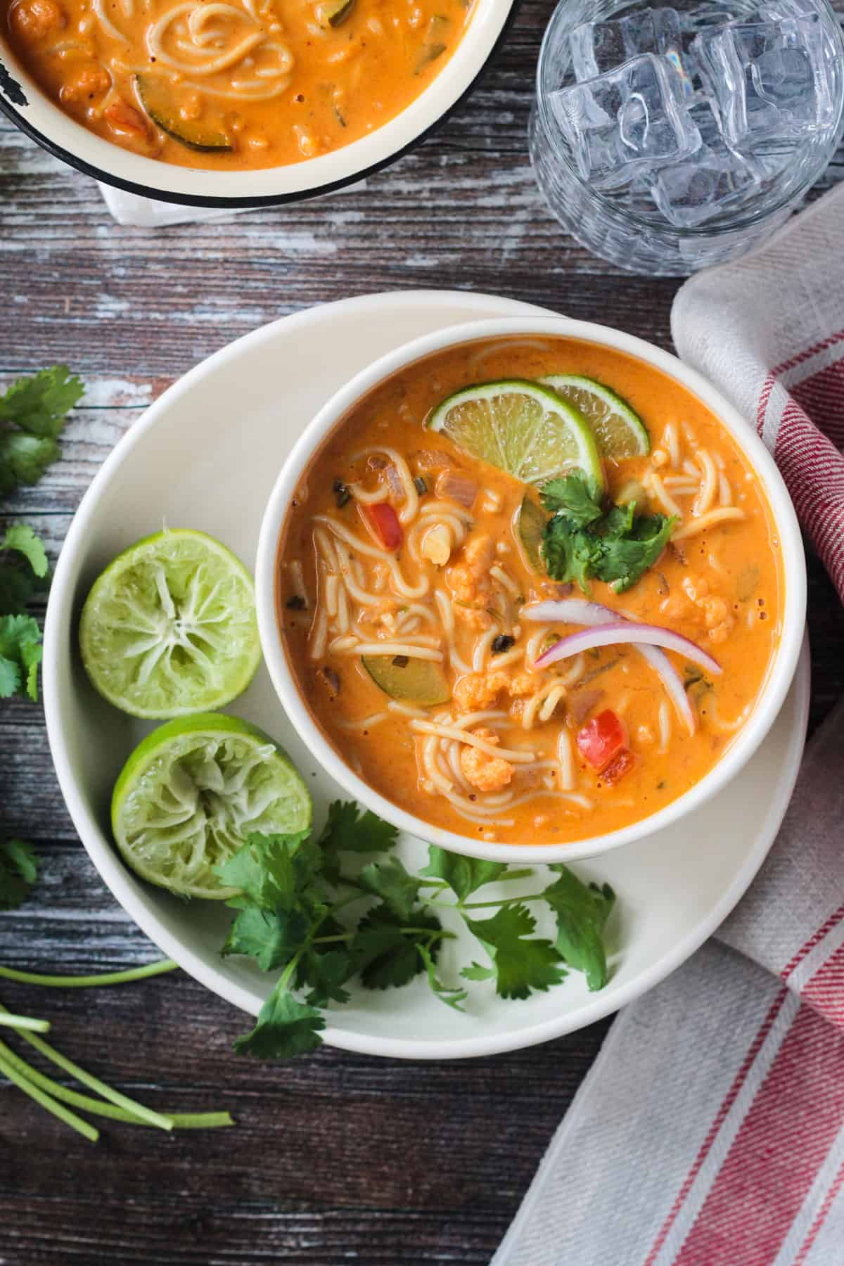 Red Curry Thai Noodle Soup in a white bowl next to lime halves and cilantro.