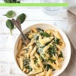 Fork in a bowl of creamy pasta garnished with fresh parsley.