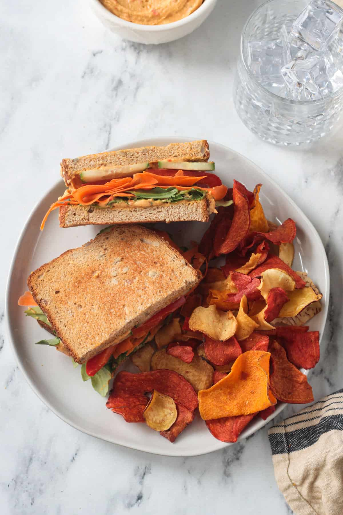 Veggie Hummus Sandwich cut in half on a plate with chips.