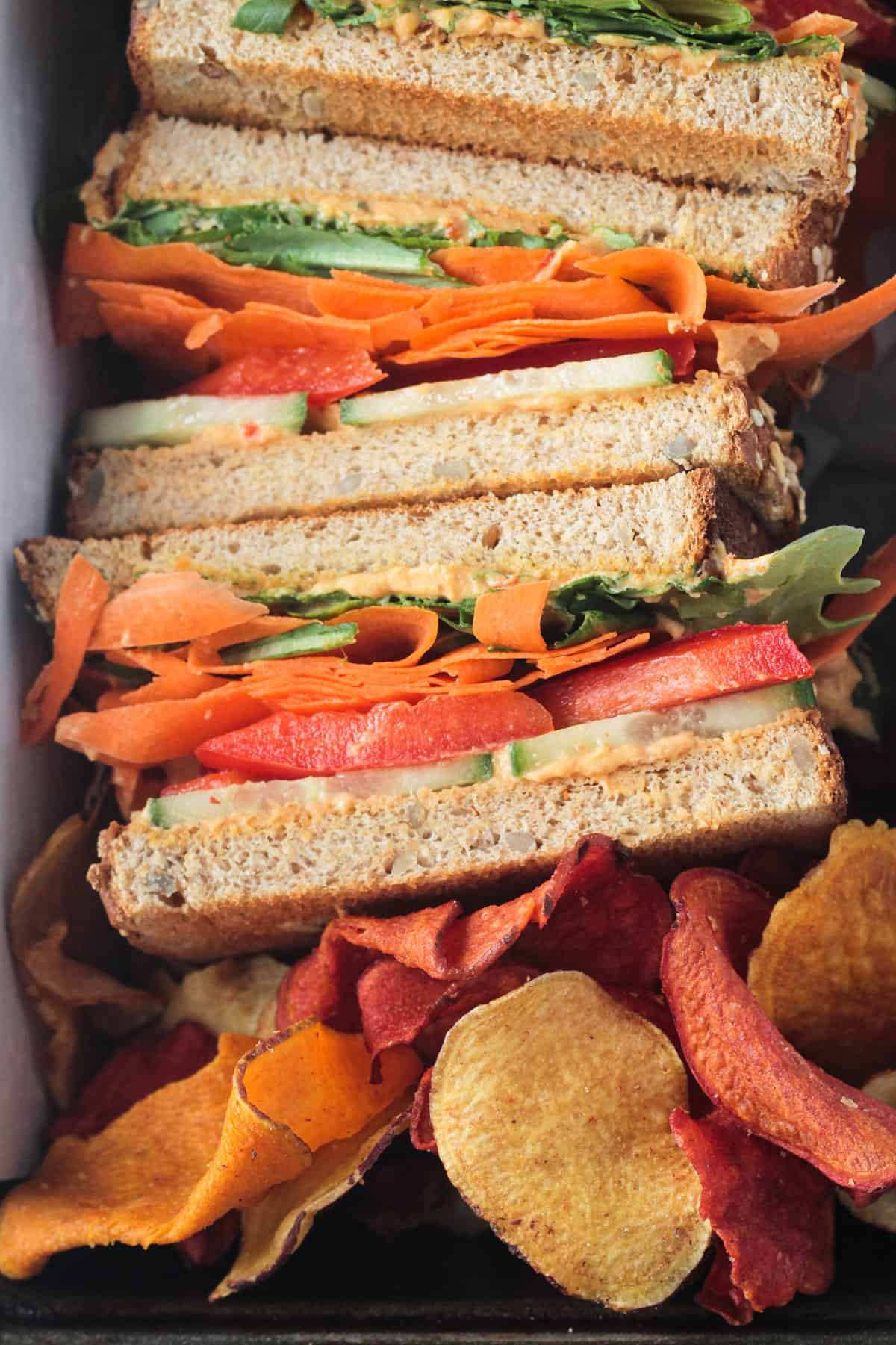 Close up of vegetables and hummus on a half of sandwich.
