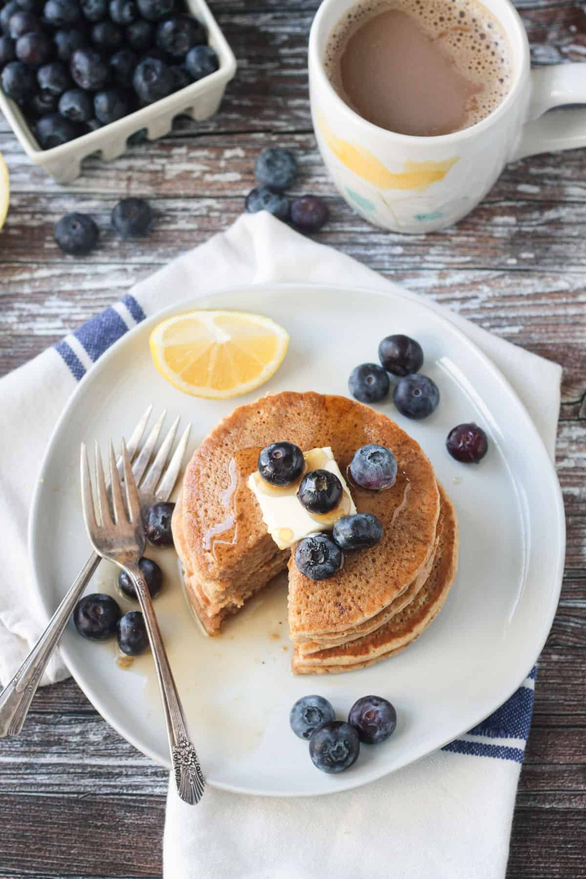 Two forks on a plate with oat flour pancakes and fresh blueberries.