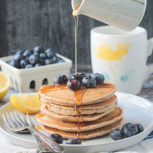 Syrup being poured onto a stack of 5 oat flour pancakes topped with blueberries.