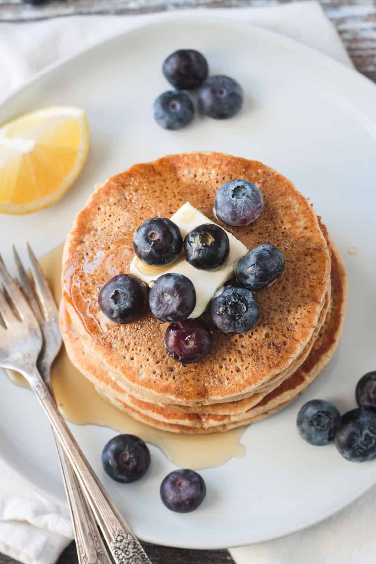 Overhead view of a stack of pancakes topped with a pat of butter and fresh blueberries.