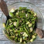 Snap peas, sweet peas, cucumbers, onion, fresh herbs, and dressing mixed in a glass bowl.