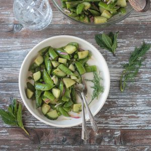 Two forks in a bowl of sugar snap pea salad.