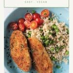 Two breaded vegan chicken cutlets on a blue plate with rice, peas, and tomatoes.